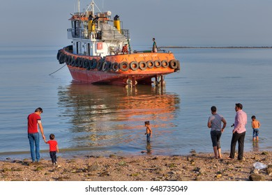 Bandar Abbas, Hormozgan Province, Iran - 16 april, 2017: The townspeople are walking along the beach of the Persian Gulf, against the backdrop of a towboat that ran aground.