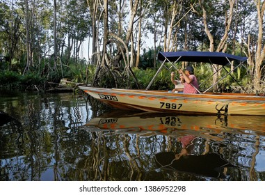 BANDAR SERI BEGAWAN, BRUNEI — APRIL 7, 2018. Tourists on a boat cruise the mangrove swamp at Pulau Ranggu on the Brunei River, looking for the proboscis monkeys that live there.