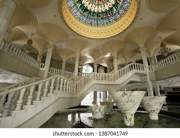 BANDAR SERI BEGAWAN, BRUNEI — APRIL 7, 2018. A colorful leaded glass dome, marble staircase and pillars, and bubbling fountains enhance the main lobby of Jame' Asr Hassanil Bolkiah Mosque.