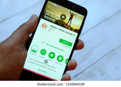 BANDAR SERI BEGAWAN,BRUNEI - JULY 25TH,2018 : A male hand holding smartphone with Udemy apps on an android Google Play Store