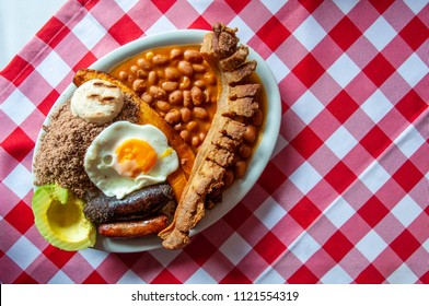 Bandeja paisa, typical dish at the Antioquia region of Colombia. It consists of chicharrón (fried pork belly), black pudding, sausage, arepa, beans, fried plantain, avocado egg, and rice.