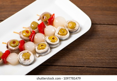 Banderillas of olives with spring onion and anchovies in a white plate on wooden table. Typical spanish food.