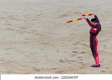 Banderillero holding banderillas in his hands and claiming attention for the bull in a bullfight
