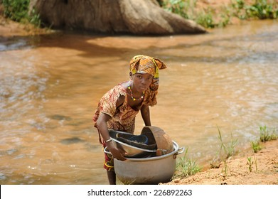 BANDIAGARA, MALI, AFRICA - AUGUST, 28, 2011 Girl doing heavy work tasks in the river
