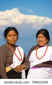 Bandipur, Nepal - December 17, 2007: Two beautifully dressed ethnic villagers dressed in clean traditional clothes stand in front of snow-capped Himalayan mountains