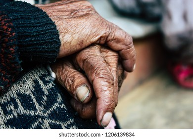 Bandipur Nepal October 17, 2018 Closeup of hands of unknown old Nepalese woman sitting front her traditional house located in the main street of Bandipur in the afternoon