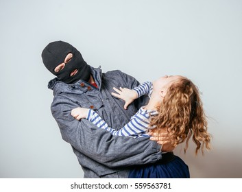Bandit in balaclava stolen child. child abduction. stealing kidnapped
