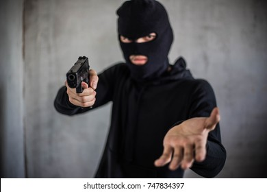 Bandit carrying a gun, wearing a black mask, robbed.