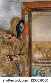 Bandit or killer in balaclava ski mask, jacket with hood, staying in abandoned building near the door and holding knife in a hand. Waiting for the victim