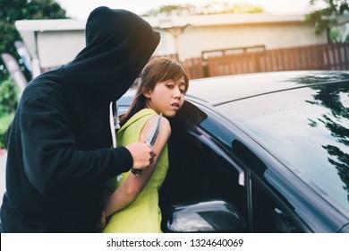 Bandit man holding handgun to hijack hostage woman shocked at car park violence concept.