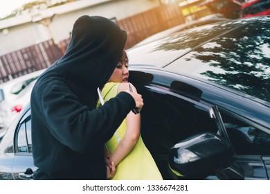 Bandit man holding handgun to hijack hostage woman shocked at parking violence concept.