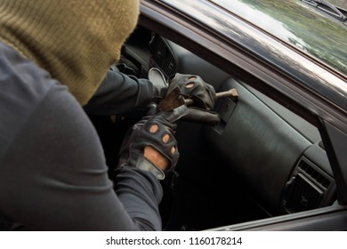 Bandit in mask breaking glove box. Carjacking concept