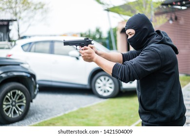 Bandit wear black mask and clothes using gun point to somewhere, concept of criminal, bandit, gangster, mafia
