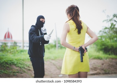 Bandit wear black mask use knife point to woman trying to rob money and hurting her but the women hide their guns behind, concept of winner, fighting, usurpation