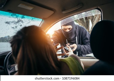 Bandits men wearing black velvet jackets are robbing cell phones from girls in cars.