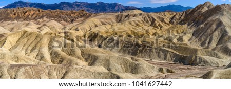 Bandlands - A panoramic view of eroded but colorful landscape in the Badlands of Death Valley, looking from a high point at Golden Canyon towards Zabriskie Point. Death Valley National Park, CA, USA.