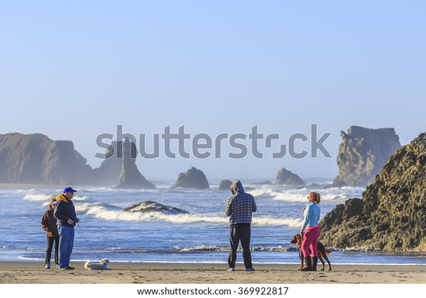 BANDON BEACH, OREGON, USA - OCTOBER 22, 2015: People with dogs enjoy views of the ocean surf
