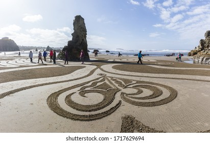 Bandon by the Sea, Oregon / USA - March 13 2020: People walking the labyrinth on the beach created by the team of Circles in the Sand with amazing detailed artwork