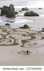 Bandon by the Sea, Oregon / USA - February 21 2020: The team of Circles in the Sand drawing a walkable labyrinth in the flat sandy beach of Face Rock State Park