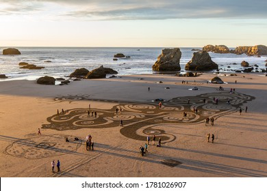 Bandon by the Sea, Oregon / USA - March 08 2020: People at sunset walking through a labyrinth on the beach of Face Rock State Park created by the team of Circles of the Sand