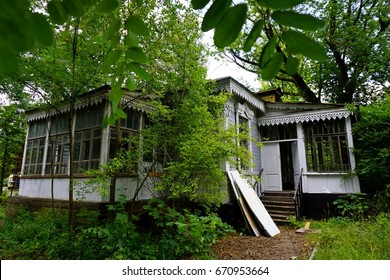 Bandoned old wooden carved house standing in middle of forest. House with summer veranda for rest, large glass windows, beautiful low relief under roof and lot of bright rooms, Pushcha-Voditsa, Kiev