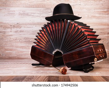 Bandoneon on wooden background with a male black hat on top, text space