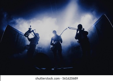 Bands silhouettes with on a concert.  Group of saxophone, guitar, trombone players performing on stage.