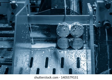The bandsaw cutting machine cutting the metal shaft with the lubricant.