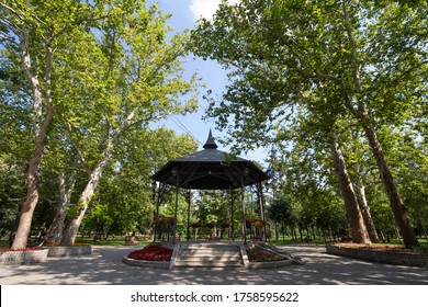 Bandstand in a city park in summer, surrounded by gardens and tall trees, with its typical round stage and metal shelter. A bandstand, or music kiosk, is a typical concert venue.
