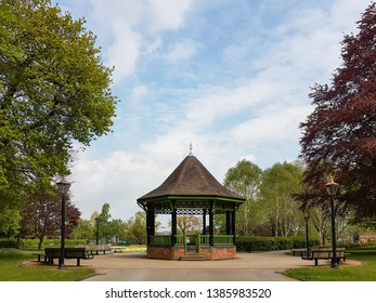A bandstand stands in Caldecott Park, Rugby surrounded by benches and antique-style lanterns on posts. It is flanked by mature beech trees.