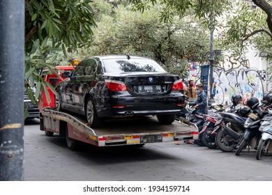 Bandung, Indonesia - February 6, 2021: The sedan cars transported by truck through Braga street.