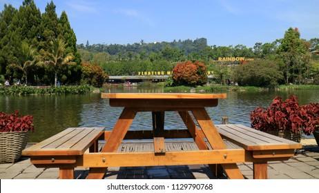 Bandung, Indonesia - July 7, 2018: Chairs and tables near man-made lakes as Floating Market Lembang, West Java.