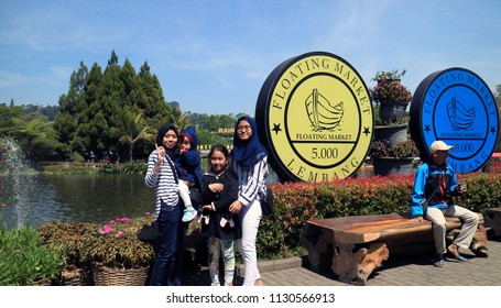 Bandung, Indonesia - July 7, 2018: Visitor taken picture in front of coin icon at Floating Market Lembang, West Java.