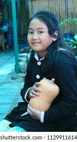 Bandung, Indonesia - July 8, 2018: Local tourist holding butternut squash or butternut pumpkin.