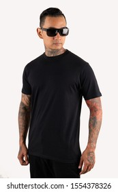 Bandung, Indonesia - October 14, 2019: A man wearing black plain t shirt isolated on white background. Hipster man with tattoo wearing black t shirt, ready for mock up design template and background.