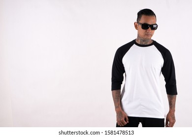 Bandung, Indonesia - October 14, 2019: hipster man with tattoo wearing sunglasses standing while posing. Ready for your mock up template design or background. Young man wearing raglan 3/4 sleeve