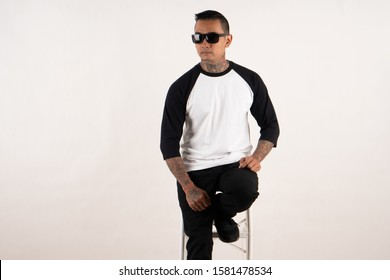 Bandung, Indonesia - October 14, 2019: Man wearing raglan 3/4 sleeve t shirt isolated on white background. Young hipster man with tattoo wearing sunglasses sitting in a chair while posing for mock up