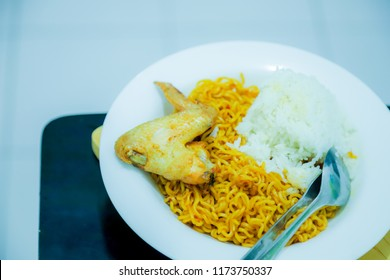 Bandung, Indonesia - September 4, 2018: Indomie Mi Goreng Jumbo (Instant Fried Noodles Jumbo) with Rice anf Fried Chicken, Big Portion. Dormitory Student Food