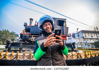 Bandung, West Java / Indonesia - July 29, 2018: A Gojek Driver Profile, an Online Transportation, Holding a Cellphone Waiting an Order from Customers with Old Steam Locomotive in the Background