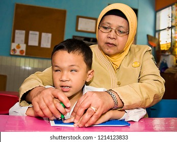 Bandung, West Java, Indonesia : teacher assisting a blind student to read braille in a extraordinary school in Bandung 09/2015 .