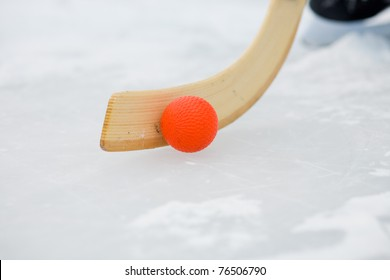 Bandy stick and Bandy ball on ice, skates in the background