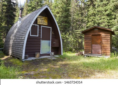 Banff, Alberta, Canada - July 22, 2019:  Primitive Backcountry Ranger Wood Log Cabin and Outhouse at Redearth Creek in Banff National Park, Canadian Rocky Mountains