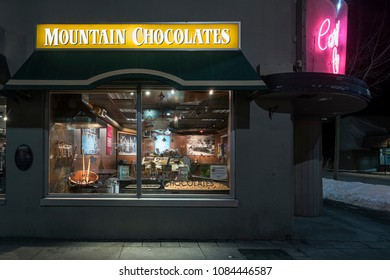 Banff, Alberta, Canada - March 08,2018:  A night view of the illuminated window of the Mountain Chocolates Shop located on Banff Avenue in Banff.  Through the window, the shop interior is visible.