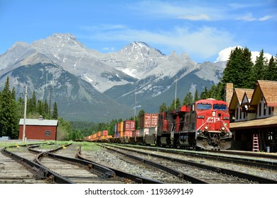Banff Alberta,Canada,July 4th 2014.A freight train travels through the train depot in Banff National park.Scenic mountain landscape in Banff Alberta.Come visit this awesome place you will like it.