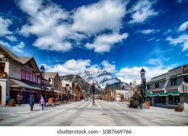 BANFF, CANADA - APRIL 12, 2018: Busy Banff Avenue in the Banff National Park with Cascade Mountain in the background. The townsite is a tourist destination renowned for its mountainous surroundings.