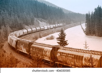 Banff, Canada, June 07, 2011: Freight train of Canadian Pacific railway moves through Canadian Rockies under the pouring rain.