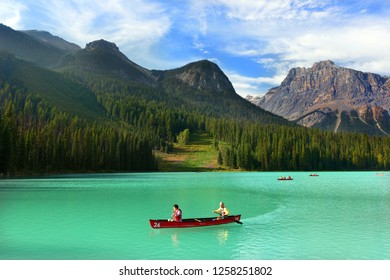 Banff, Canada - Sep 10th 2018 - A mature couple having fun in a kayak in the green color lake Emerald with beautiful pine trees in the background in Canada