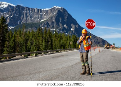 Banff National Park, Alberta, Canada - June 20, 2018: Traffic Control Flagger is working on the Highway during a sunny summer day.