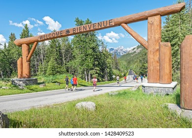 Banff National Park, Alberta Canada - June 16, 2019:  runners in the Banff Marathon pass under the welcome sign on the Bow Valley Parkway