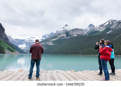 Banff NP, Alberta / Canada - June 23 2019: Tourist busy on their technology forgetting to just enjoy the beautiful Lake Louise.